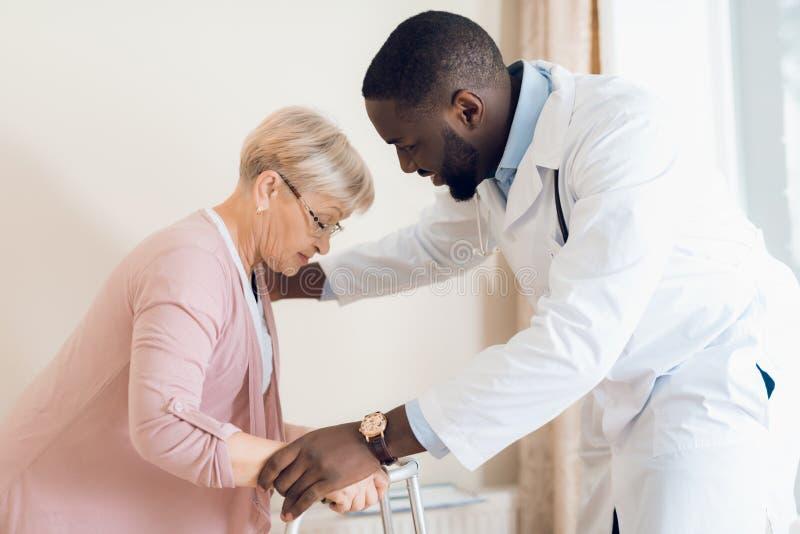 Doktorn hjälper att få ut ur säng en äldre kvinna i ett vårdhem arkivbilder