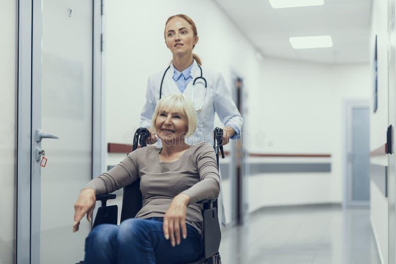Doktorn hjälper den ogiltiga damen i sjukhuset fotografering för bildbyråer