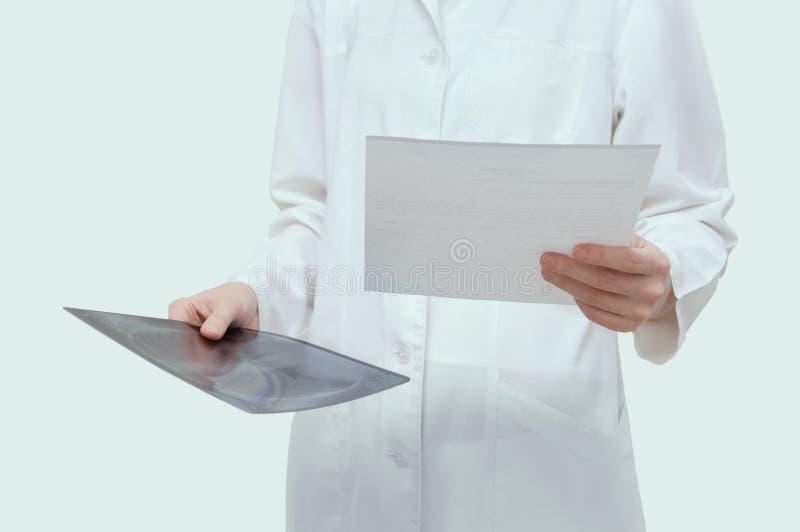 Doktorn i det vita labblaget rymmer röntgenstrålen och formen för provresultat i vit på vit bakgrund arkivbild