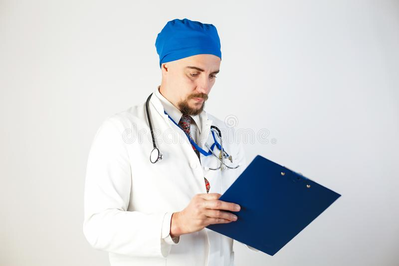 Doktorn i ett vitt lag skriver datan till journalen Vit bakgrund royaltyfri fotografi