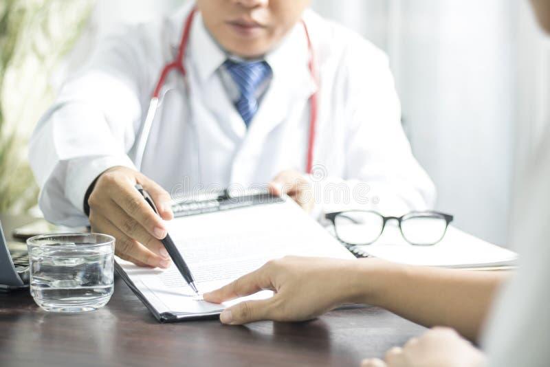 Doktorn introducerar patienten som undertecknar på sjukdomshistorier för trea royaltyfria bilder