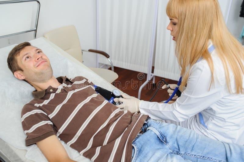 Doktorn konsulterar patienten med stetoskopet p? hans hand royaltyfri fotografi