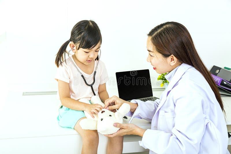 Doktorn kontrollerar nallebjörnen Den kvinnliga doktorn undersöker flickorna Undersökande liten flicka för kvinnlig doktor med arkivfoton