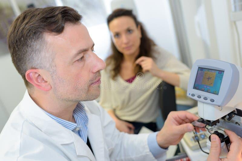 Doktorn kontrollerar tålmodiga ögon genom att använda den ögon- apparaten arkivbild