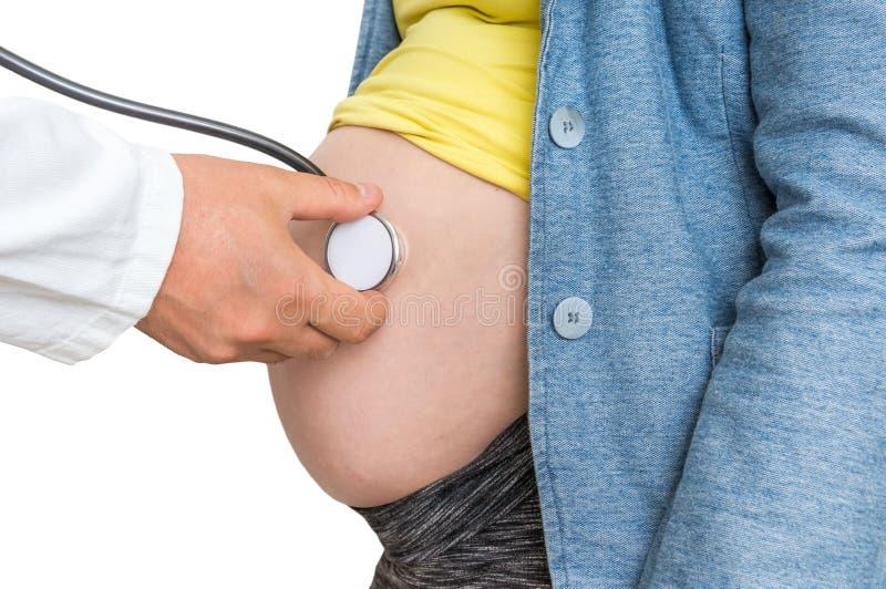 Doktorn lyssnar till hjärtslaget behandla som ett barn av gravid kvinna royaltyfria foton