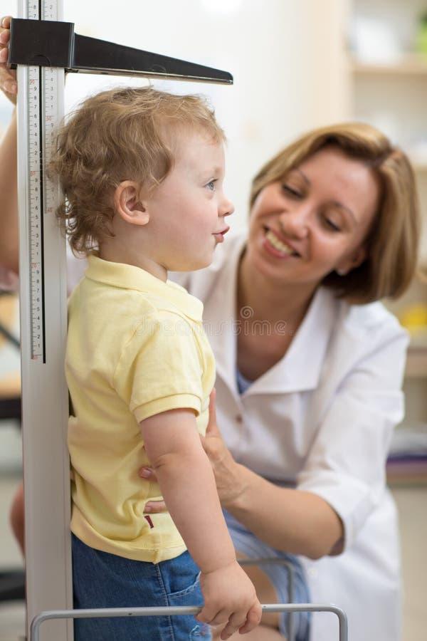 Doktorn mäter tillväxt som ler barnpojken i det medicinska kontoret, profil arkivfoton