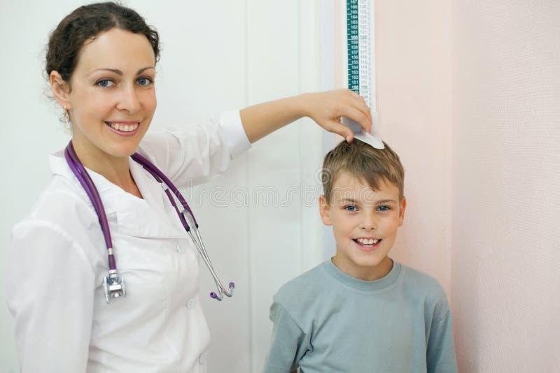 Doktorn mäter tillväxtpojken i medicinskt kontor arkivfoto