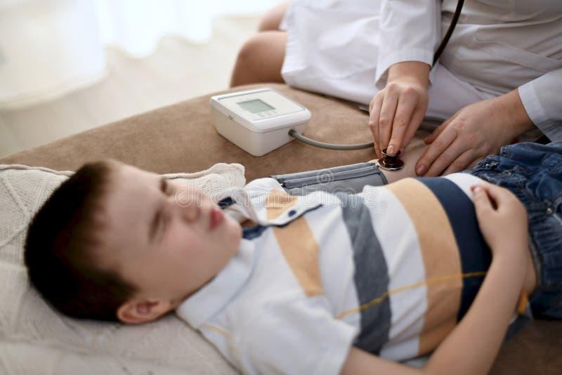 Doktorn mäter trycket av en skelad pojke royaltyfria bilder