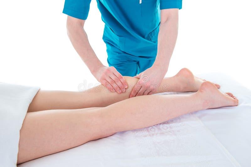 Doktorn masserar kvinnabenet på sjukgymnastikperiod royaltyfri fotografi
