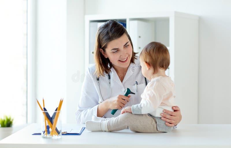 Doktorn med behandla som ett barn och otoscopen på kliniken royaltyfri bild