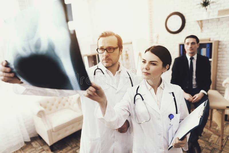 Doktorn med stetoskopet och sjuksköterskan undersöker röntgenstrålen av affärsmannen, av patienten royaltyfri foto