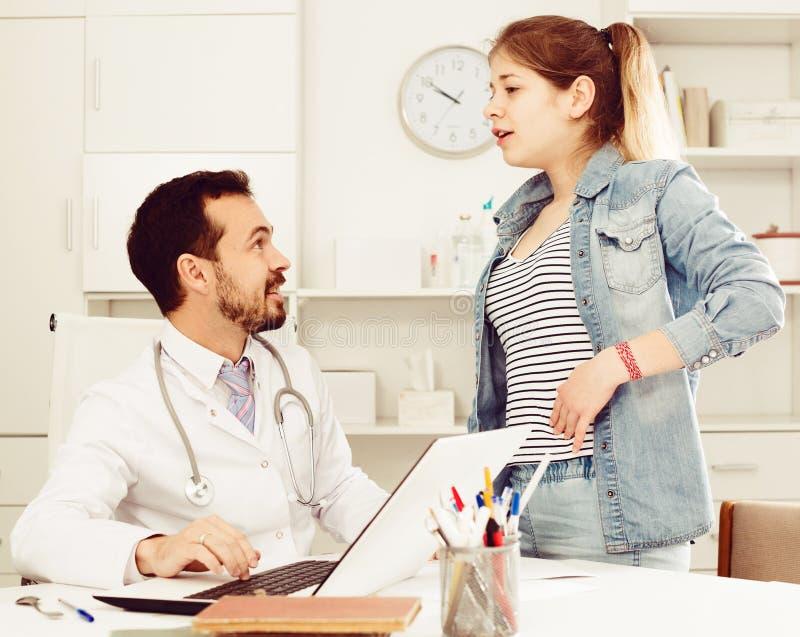 Doktorn och flickan med smärtar i sida arkivfoton