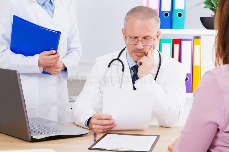 Doktorn på tabellen undersöker resultaten av hans patient analyserar, doc i medicinskt kontor arkivbild