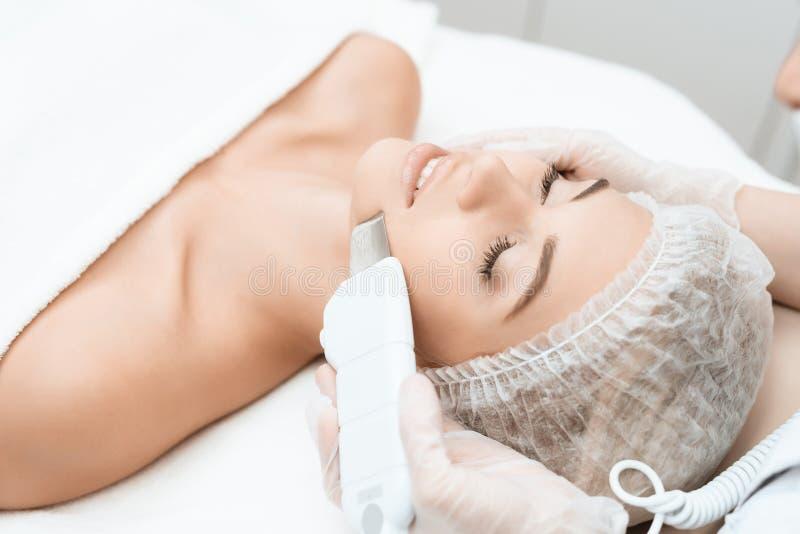 Doktorn rentvår huden för kvinna` s med en special medicinsk apparat Kvinnan kom till tillvägagångssättet av laser-hårborttagning royaltyfria foton