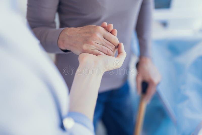 Doktorn rymmer den tålmodiga handen i sjukhuset royaltyfri foto