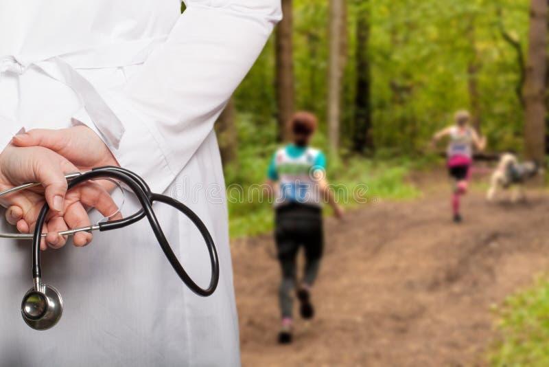 Doktorn satte hans händer med stetoskopet bak hans baksida på ett b fotografering för bildbyråer
