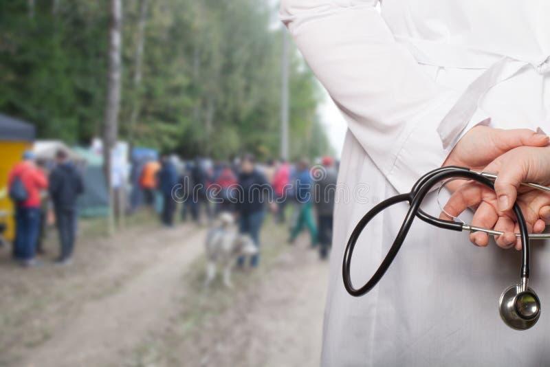 Doktorn satte hans händer med stetoskopet bak hans baksida på ett b royaltyfri foto