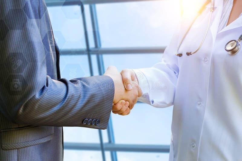 Doktorn skakar händer med patienten arkivbilder