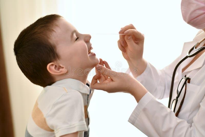 Doktorn skojar med barnet royaltyfri bild