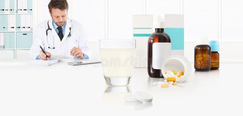 Doktorn skriver det medicinska receptet på ett skrivbordkontor med exponeringsglashuvudvärkstablettminnestavlor, piller och drogf arkivbild