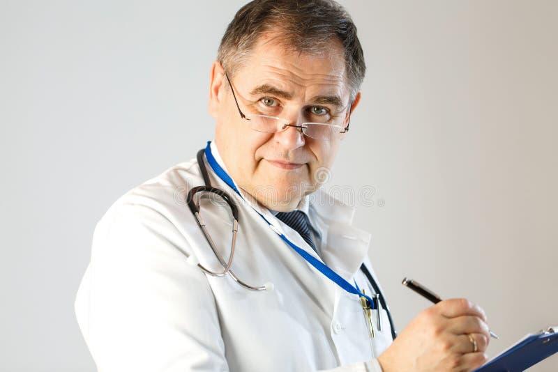 Doktorn skriver ett recept och blickar in i framsidan arkivfoton
