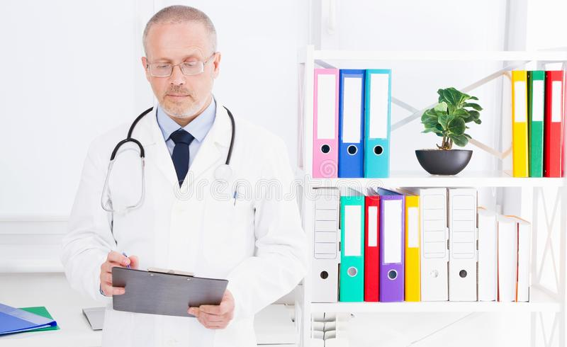 Doktorn skriver något i mapp i klinikkontoret royaltyfri bild