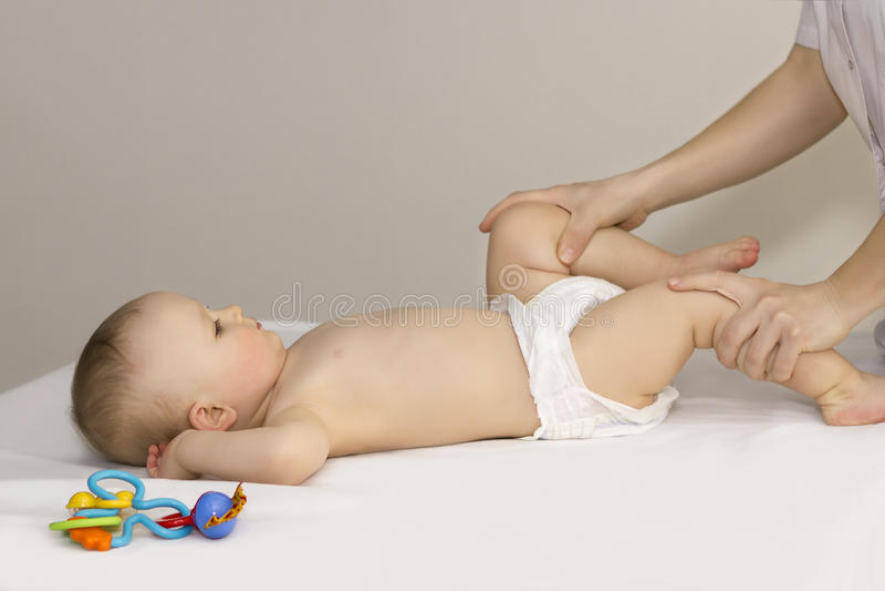 Doktorn som gör massagefot, behandla som ett barn royaltyfri bild