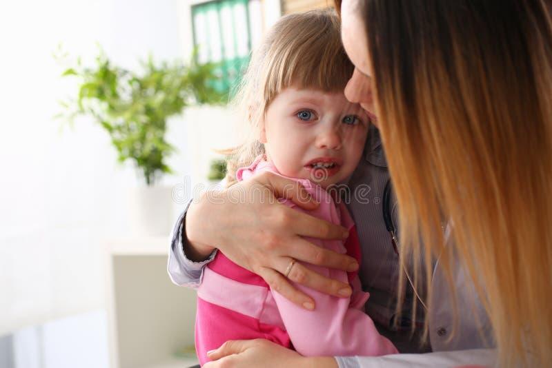 Doktorn som kramar förskräckt gråt behandla som ett barn lite, flickan som besöker hennes kontor royaltyfri bild