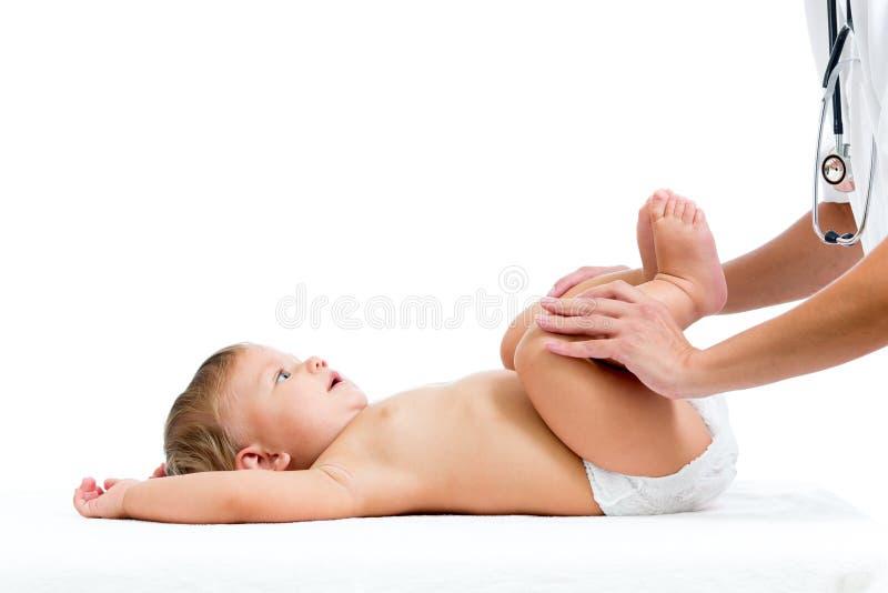 Doktorn som masserar eller gör gymnastik, behandla som ett barn flickan royaltyfri foto