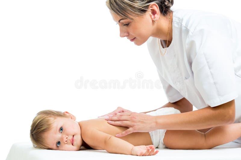 Doktorn som masserar eller gör gymnastik, behandla som ett barn flickan fotografering för bildbyråer