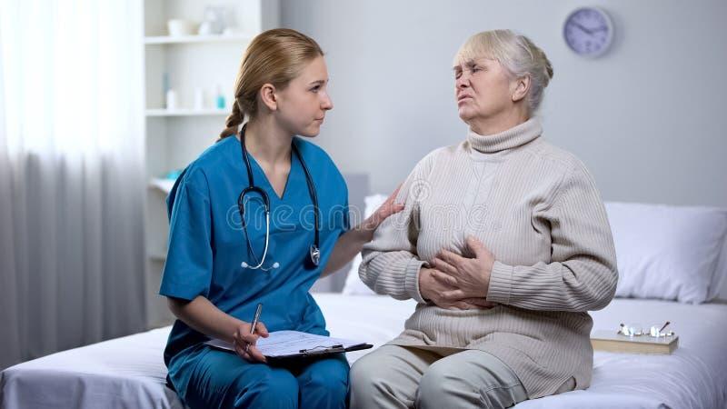 Doktorn som stöttar den äldre patienten som skriver diagnos i sjukdomshistorier, smärtar arkivbild