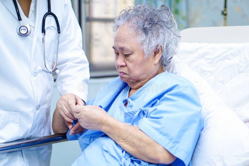 Doktorn som trycker på den asiatiska höga eller äldre kvinnapatienten för den gamla damen med förälskelse, omsorg som hjälper, up arkivbilder
