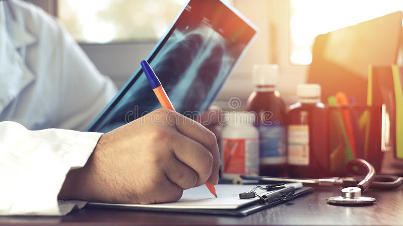 Doktorn som undersöker MRI-bildläsningen av lungorna och skriver en avslutning arkivfoton