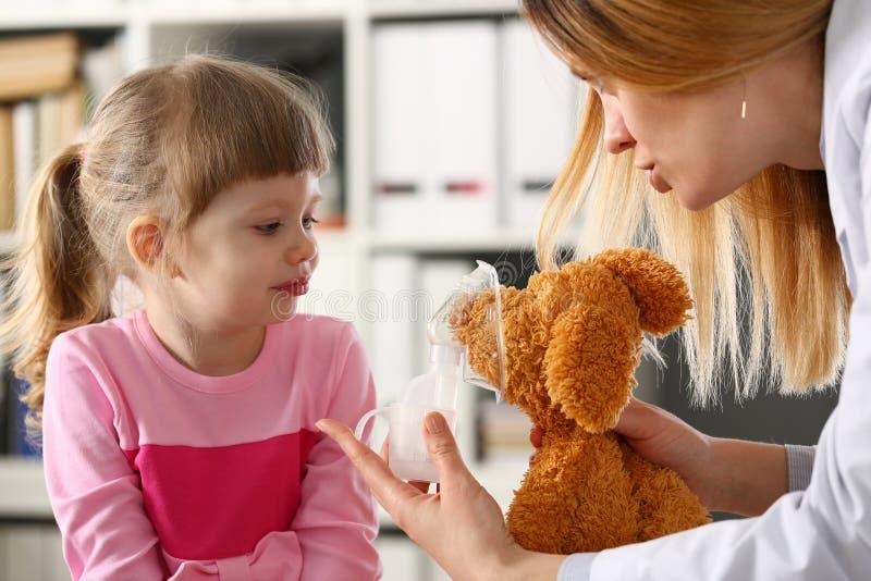 Doktorn spelar med den lilla patienten som ger inhalatorn till leksaken royaltyfri fotografi