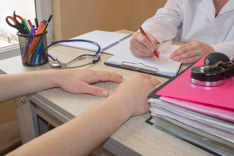 Doktorn talar med den kvinnliga patienten och gör anmärkningar, medan sitta i hans kontor arkivfoton