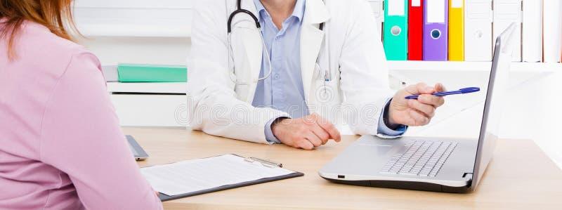 Doktorn talar med kvinnapatienten och sitter i medicinskt kontor royaltyfria foton