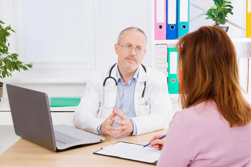 Doktorn talar med kvinnapatienten och sitter i medicinskt kontor Man i den vita likformign Medicinsk försäkring kopiera avstånd royaltyfria foton