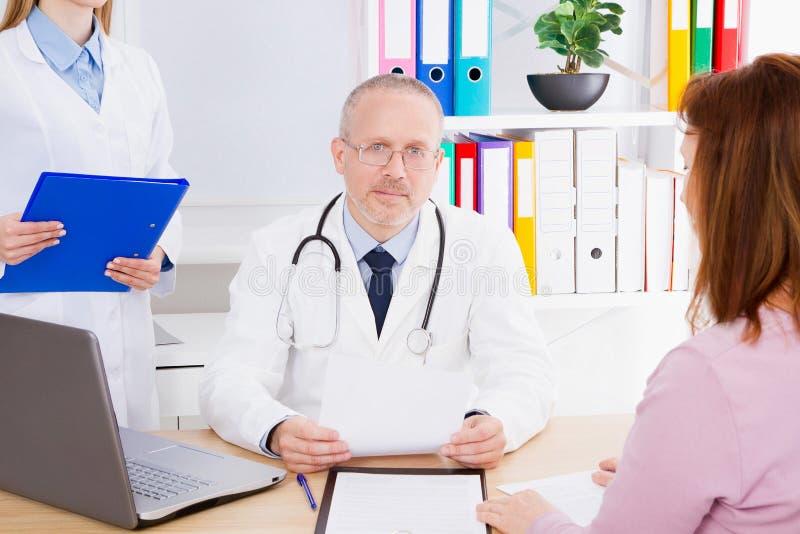 Doktorn talar med kvinnapatienten och sitter i medicinskt kontor Man i den vita likformign Medicinsk försäkring kopiera avstånd fotografering för bildbyråer