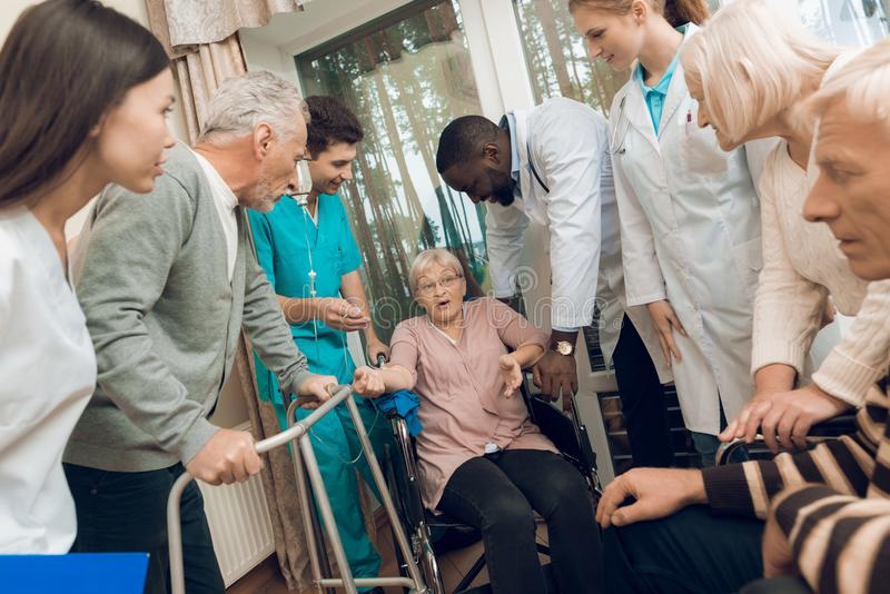 Doktorn talar till en äldre kvinna i ett vårdhem fotografering för bildbyråer