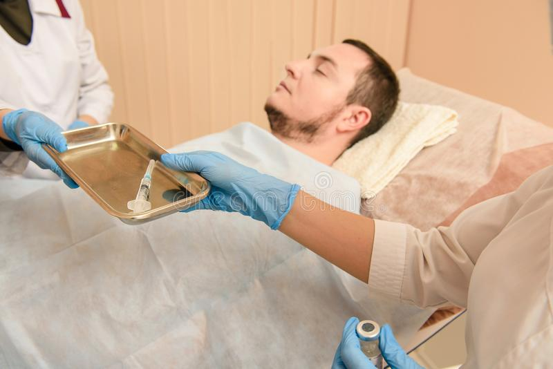 Doktorn tar en injektionsspruta royaltyfria foton