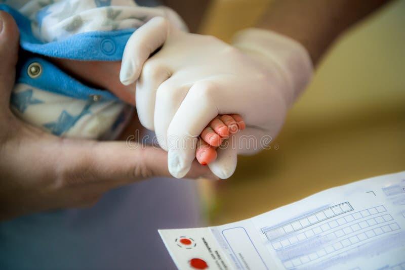 Doktorn tar ett blodprov i newborns royaltyfria foton