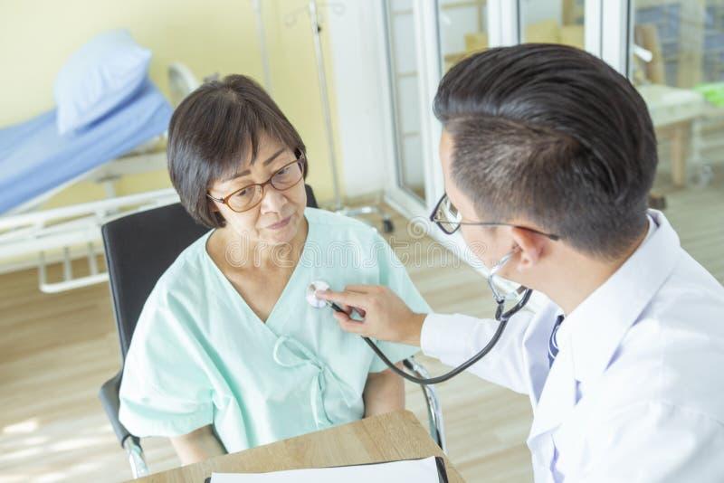 Doktorn undersöker den äldre kvinnapatienten som använder en stetoskop arkivfoton