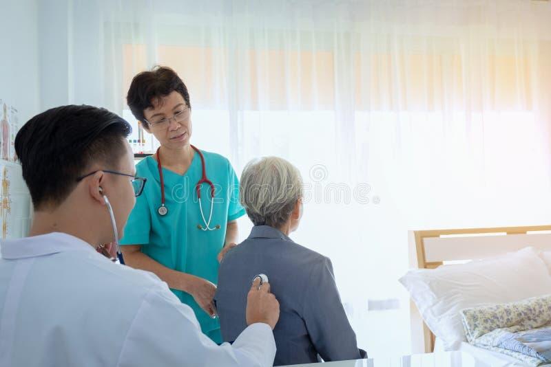 Doktorn undersöker den höga patienten som använder en stetoskop fotografering för bildbyråer