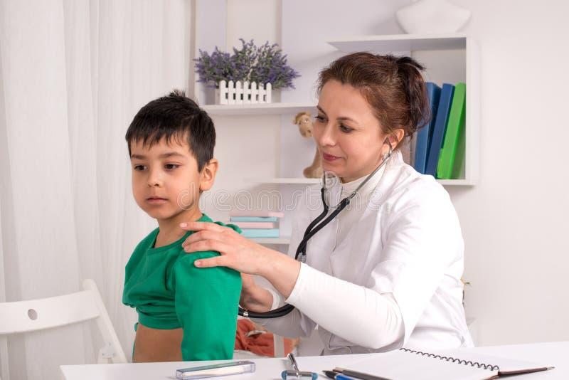 Doktorn undersöker det sjuka barnet i ett kontor arkivfoton