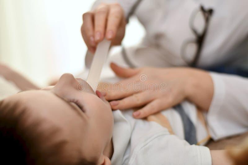 Doktorn undersöker halsen av ett barn arkivbild