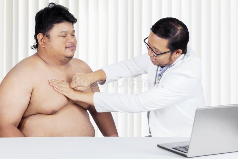 Doktorn undersöker hjärtan av den överviktiga patienten arkivfoto