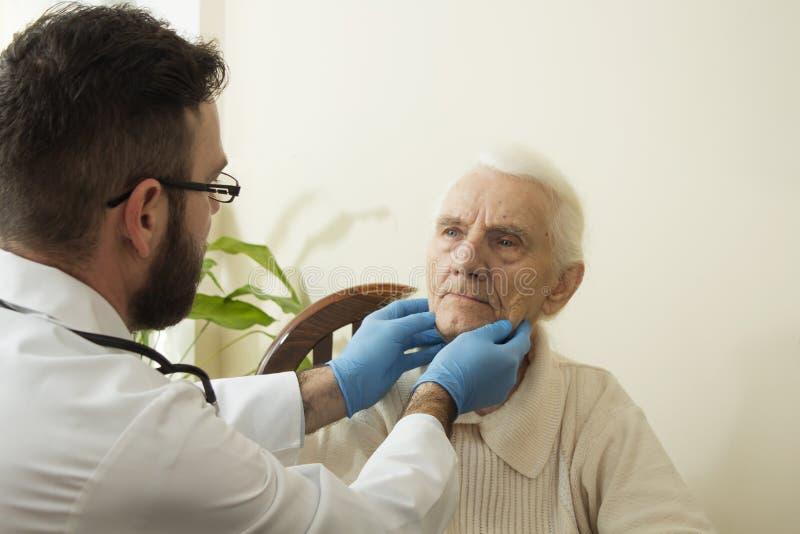 Doktorn undersöker lymfaknutpunkterna på halsen av en gammal kvinna arkivbild