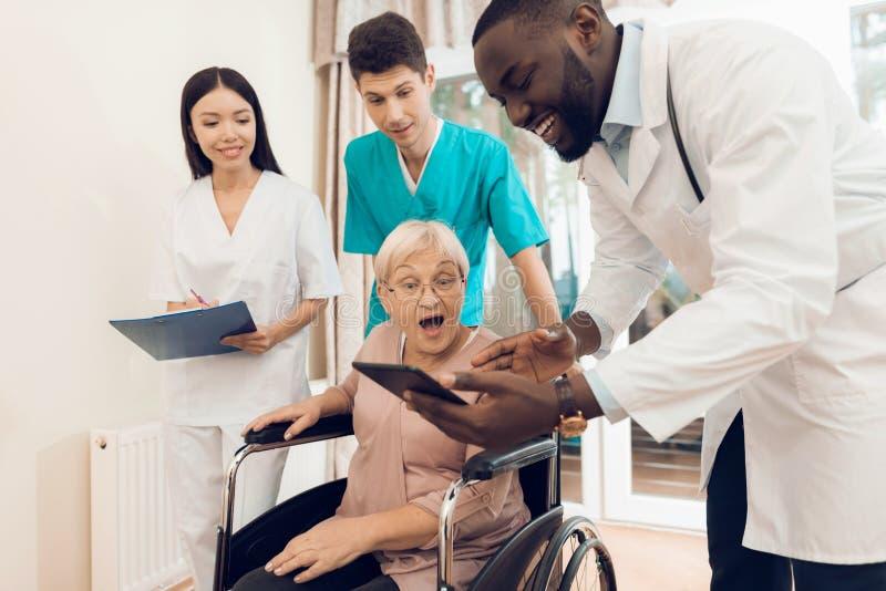 Doktorn visar något på minnestavlan till en äldre patient i ett vårdhem fotografering för bildbyråer