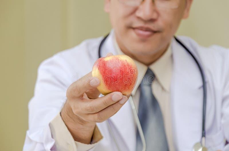 Doktorrechte hand, die frischen Apfel nach vorn hält stockbilder