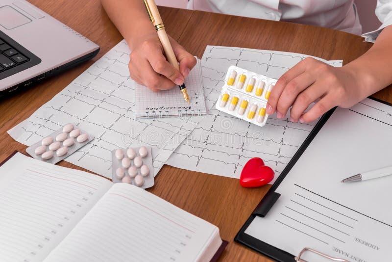 Doktors händer med det olika piller, hjärta och receptet arkivfoto